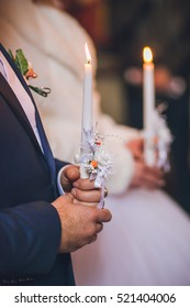 Wedding candles in the hands of the bride