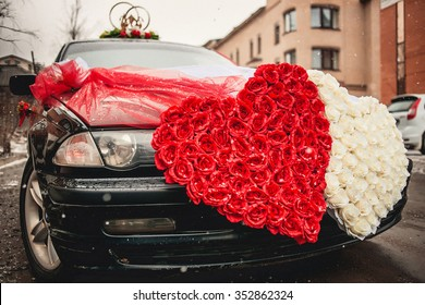 Wedding car decorated with two hearts made of flowers roses.