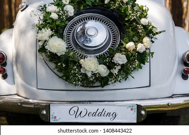 """Wedding car with a decorations and the word """"Wedding"""". Just married car for the bride and groom"""