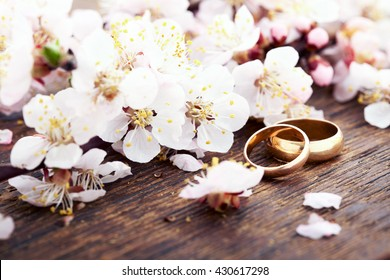 Wedding card, Wedding rings. Valentine's Day greeting. Wedding bouquet, background. Flowering branch with white delicate flowers on wooden surface. Declaration of love, spring. Empty wooden tabletop