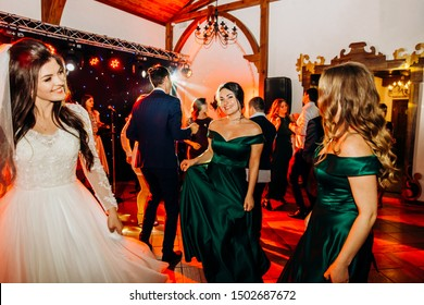 Wedding celebration. The bride and her friends dance on the dance floor