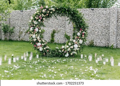 Wedding ceremony aisle with an arch made of flowers and greenery. Backyard wedding venue.