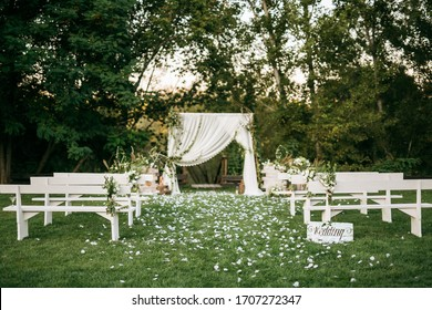 Wedding ceremony aisle with an arch made of chiffon white textile and flowers and long white wooden benches on green grass. Backyard wedding venue.