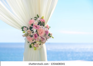 Wedding ceremony. Arch, decorated with flowers on the lawn, beach background, sea in summer.