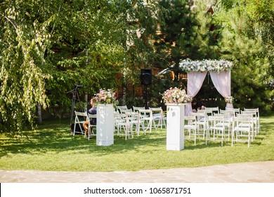 Wedding ceremony in beautiful garden. Elegant decoration of wedding ceremony in pretty pink colors. Outdoors wedding ceremony with beautiful white furniture