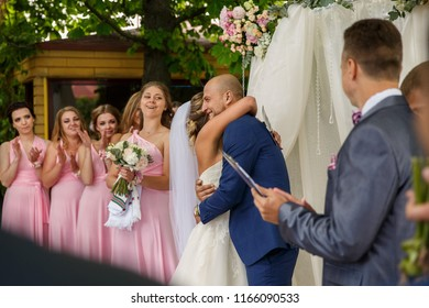 Wedding ceremony. Bride and groom embracing at wedding ceremony on bridesmaids background.
