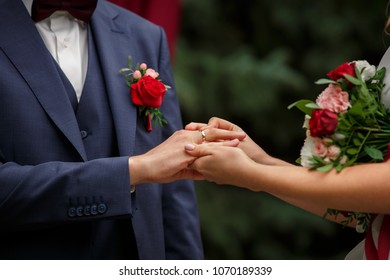 Wedding ceremony. Bride and groom are exchanging wedding rings on wedding arch background, newlyweds couple and just married couple in love. Marriage and marsala or red wedding concept