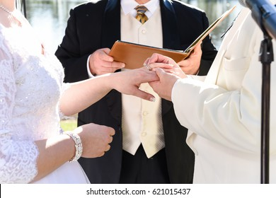 Wedding ceremony, bride, groom, Officiant, outdoors, exchanging rings