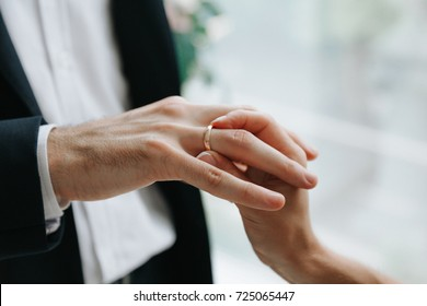 Wedding ceremony. Bride puts  the engagement ring on  to the groom. Wedding day
