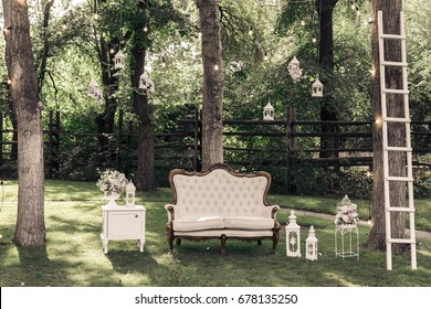 Wedding ceremony decorations bouquets of roses, sofa, staircase in a park outdoors.
