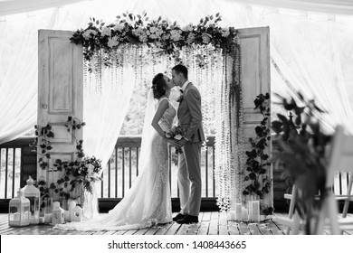Wedding ceremony. Elegant wedding couple kissing near wedding arch. Black and white photo of bride and groom in love