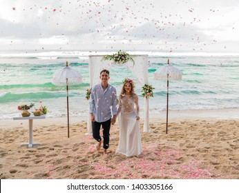 Wedding ceremony with falling petals on tropical beach