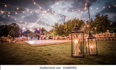 Wedding Ceremony with flowers outside in the garden with hanging lights