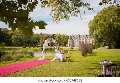 Wedding ceremony at a french Chateau. Wedding arch with flowers and table.