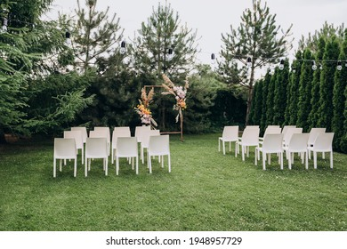 Wedding ceremony in the garden for the bride and groom. Elegant decoration of a wedding ceremony outdoors. Outdoor wedding ceremony. Wooden guest chairs