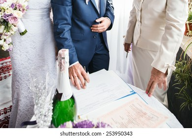 Wedding ceremony. The groom in a registry office is ready to put his signature
