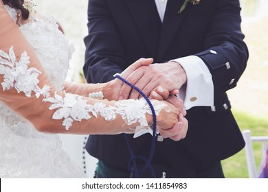 Wedding ceremony hands tied in nautical rope handfasting vows
