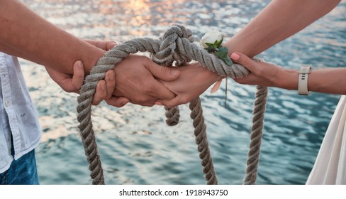 Wedding ceremony handsbye, wedding anniversary, valentine's day tied in nautical rope handfasting vows, as a sign of eternal love and veneration.