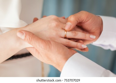Wedding ceremony. He puts the engagement ring on his finger close-up. Bride and groom