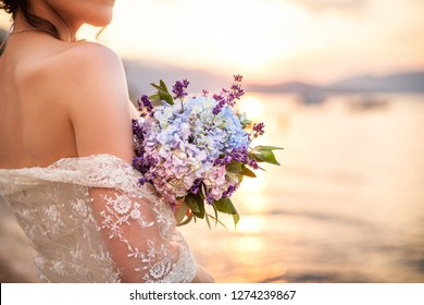 Wedding ceremony on ocean beach. Bride holds wedding bouquet from hydrangea and lavender flowers. Background of sea and sunset. Girl is dressed in white lace wedding dress.