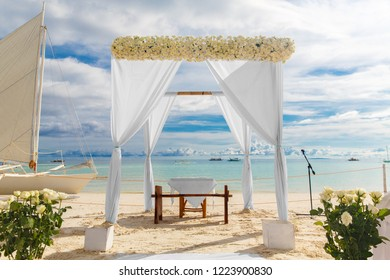 Wedding ceremony on a tropical beach in white. Arch decorated with flowers on the sandy beach. Wedding and honeymoon concept.