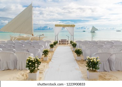 Wedding ceremony on a tropical beach in white. The arch is decorated with flowers on the sandy beach, decorated chairs for guests, sand castle and yacht in the sea. Wedding and honeymoon concept.