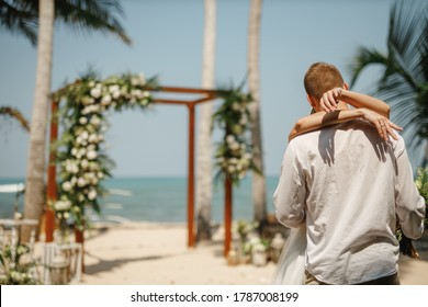 Wedding ceremony on a tropical beach. Happy groom and beautiful bride kissing under the arch decorated with flowers on tropical sand beach wih palms. Sea on the background