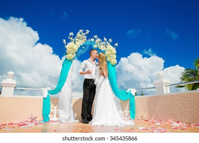 Wedding ceremony on a tropical beach in blue. Happy groom and bride under the arch decorated with flowers on the on hotel, tropical sea in the background.
