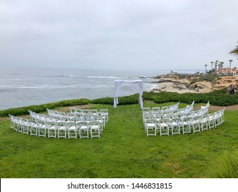 Wedding ceremony setting  with white chairs and arch in the garden in front of the ocean, wedding concept, La Jolla, California, USA