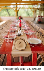 Wedding. The chairs and table for guests, decorated with candles and flowers, served  and covered with a tablecloth. Wooden sign with table number. Decoration with garland of light bulbs.
