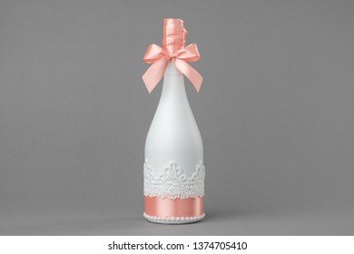 Wedding champagne bottle decorated with lace and ribbon.