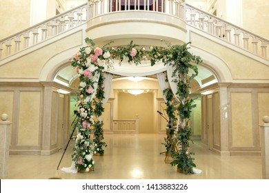 Wedding chuppah decorated with fresh flowers indoor banquet hall of wedding ceremony. Luxury wedding florist decoration artwork.