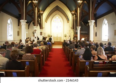 A wedding in a church, looking down the aisle during the ceremony