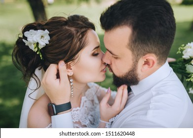 Wedding closeup portrait of beautiful newlyweds. Stylish bearded groom gently hugs and strokes a pretty brunette bride. Photography and concept. A tender kiss.