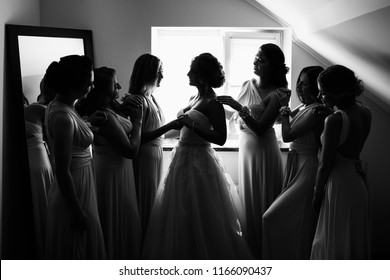 Wedding concept. Black and white photo, bride and bridesmaids posing in hotel or fitting room at wedding day.