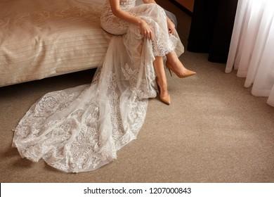 Wedding concept. Bride in high heels bridal shoes holding wedding dress