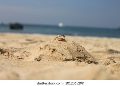 Wedding concept - Wedding rings lie on sand castle and mountain at Patong Beach Thailand