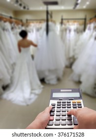 Wedding cost concept by calculator and the bride blur in background
