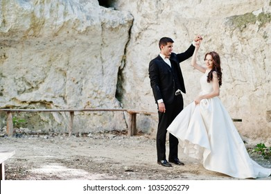 Wedding couple against cave at summer day.