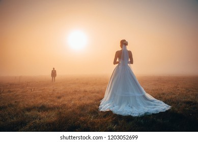 Wedding couple in autumn morning. Brdie waiting groom in orange misty sunrise light. Romantic, mariage or valentine photo. Orange edit space