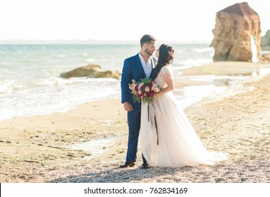 wedding couple. Beautiful bride and groom. Just merried. Close up. Happy bride and groom on their wedding hugging. Groom and Bride on the beach near the sea. wedding dress.