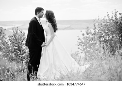 Wedding couple at breathtaking landscape with rock and lake.