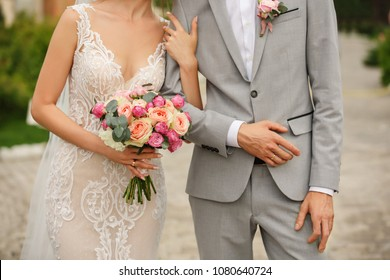 Wedding couple. Bride with wedding bouquet holds the groom's arm. Stylish newlywed couple. Marriage concept