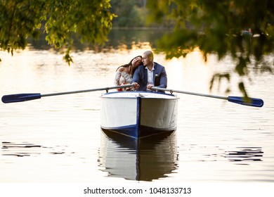 Wedding Couple Bride and Groom in the Park Pond in the Pleasure Boat.  posing in boat at lake in forest