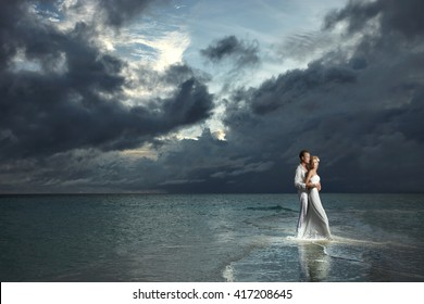 Wedding couple, bride and groom standing in sexual embrace under threatening clouds at sunset. Magnificent evening twilight.