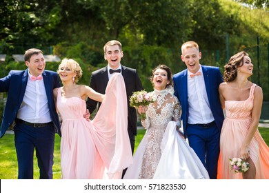Wedding couple, bridesmads and groomsmen  pose happy on green lawn