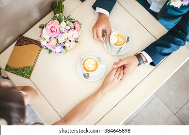 Wedding couple at cafe, top view. Man holds woman's hand, drinks espresso. Bride and groom coffee break dating gift, bouquet on table.