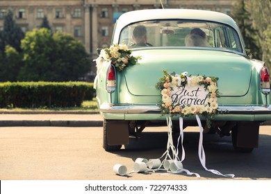 Wedding couple in car decorated with plate JUST MARRIED and cans outdoors