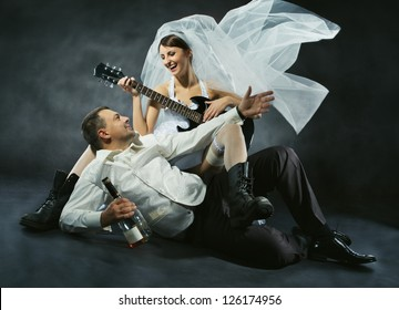 Wedding couple celebrating, singing, drinking and playing guitar. Bride in rock style.