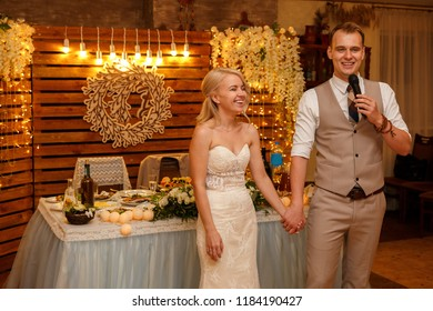 Wedding couple. Cheerful newlyweds holding each other hands, during groom's speech with a microphone. Wedding party at the restaurant